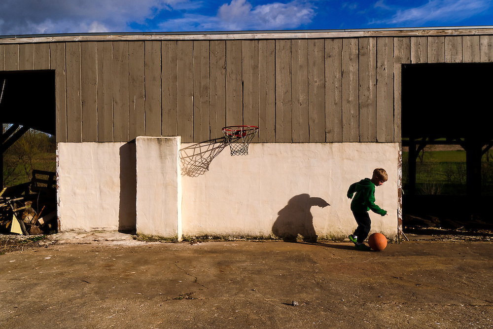photo by Matt Roth.Wednesday, April 11, 2012..Miles Shriver, 5, plays with a basketball under a hoop, installed low to the ground on an outside barn wall. ..Ron Shriver grew up on a large farm house in Pleasant Valley, Maryland, a small township outside Westminster. After his lease was up, he moved back to his parent's home with his two children Rory and Miles, living temporarily in their basement before graduating from McDaniel College in May. After tossing his graduation cap, he and his children will drive cross country to meet up with his wife who has been working on her graduate degree in Alaska. ..Ron Shriver is a retired marine staff sergeant. He is also the first in his family to attend college, thanks to the New G.I. Bill. His wife, a fellow retired Marine, is finishing up graduate school in Alaska. After Ron gets his undergraduate degree from McDaniel College in May, he plans to drive to Alaska with is two children Rory, 6, and Miles, 5. For the move Ron got rid of most of his family's belongings, and after his lease was up, he and his children moved back into his parent's farmhouse.