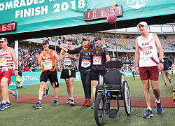 10062018 (Durban) Athletes helping Grant in the middle making his way to the finnish line at the Mosses Mabhida stadium venue during the Comrades Marathon on Sunday as Bong'musa Mthembu and Ann Ashworth ensured that the coveted titles remained on these shores.<br /> Picture: Motshwari Mofokeng/African News Agency/ANA