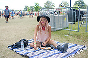 A young woman enjoys her lunch during the Bonnaroo Music and Arts Festival in Manchester, TN