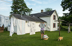 "Laundry hangs outside the home of Marilyn Mullens in Cool Ridge, West Virginia, where mountaintop-removal mines are abundant. Mountaintop Removal is a method of surface mining that literally removes the tops of mountains to get to the coal seams beneath. It is the most profitable mining technique available because it is performed quickly, cheaply and comes with hefty economic benefits for the mining companies, most of which are located out of state. Mullens organized the Memorial Day protest against mountaintop-removal mining: ""We just want people to be aware. Know that every time you turn on a light switch . . . someone here is paying for that with dirty water, with air that they can't breathe."" © Ami Vitale"