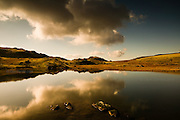 Large Cumulus clouds in afternoon sunlight reflect in the mirror calm waters of Llyn y Cwn lake on the sunlit col between Glyder Fawr an Y Garn, Snowdonia, North Wales