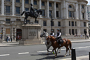 On US President Donald Trumps first day of a controversial three-day state visit to the UK by the 45th American President, mounted British Met Police officers on horseback pass the statue of Commander-in-Chief of the British Army, George Duke of Cambridge, in Whitehall, on 3rd June 2019, in London England.