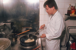 Chef using wok to stir fry food in kitchen of Chinese restaurant,