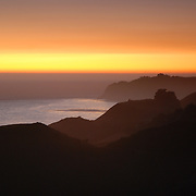 California's Coast is about 840 miles long extending from Mexico to Oregon.  Cliffs and coves abound along the Central Coast south of Monterey, California near Big Sur.  Clouds usually enhance the orange glow of sunsets.  Here the cloudless skies reveal a band of orange light.