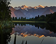 Sunset shines on Mount Tasman and Aoraki/Mount Cook (left to right) which reflect in Lake Matheson, South Island, New Zealand. In 1990, UNESCO honored Te Wahipounamu - South West New Zealand as a World Heritage Area.
