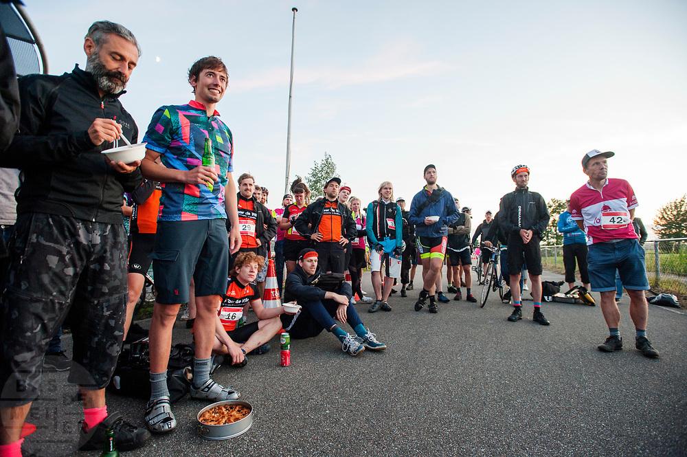 Koeriers wachten tijdens de prijsuitreiking. In Nieuwegein wordt het NK Fietskoerieren gehouden. Fietskoeriers uit Nederland strijden om de titel door op een parcours het snelst zoveel mogelijk stempels te halen en lading weg te brengen. Daarbij moeten ze een slimme route kiezen.<br /> <br /> Messengers are waiting at the prize giving. In Nieuwegein bike messengers battle for the Open Dutch Bicycle Messenger Championship.