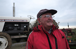 © Licensed to London News Pictures. <br /> 30/11/2014. <br /> <br /> Boulby, United Kingdom<br /> <br /> James Jobson from Hartlepool poses in front of his David Brown Selectamatic 990 tractor at the start of the ploughing match that takes place each year on fields next to the picturesque Yorkshire coastline near Staithes. Farmers attend each year to demonstrate their ploughing skills and to help raise money for charity with proceeds from this year going to Charlie Brown Cancer Care in Newcastle.<br /> <br /> <br /> Photo credit : Ian Forsyth/LNP