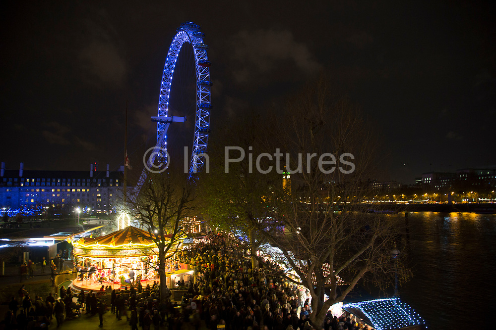 View of the Southbank during the busy Christmas season, towards the London Eye and Westminster across the River Thames.  The South Bank is a significant arts and entertainment district, and home to an endless list of activities for Londoners, visitors and tourists alike.