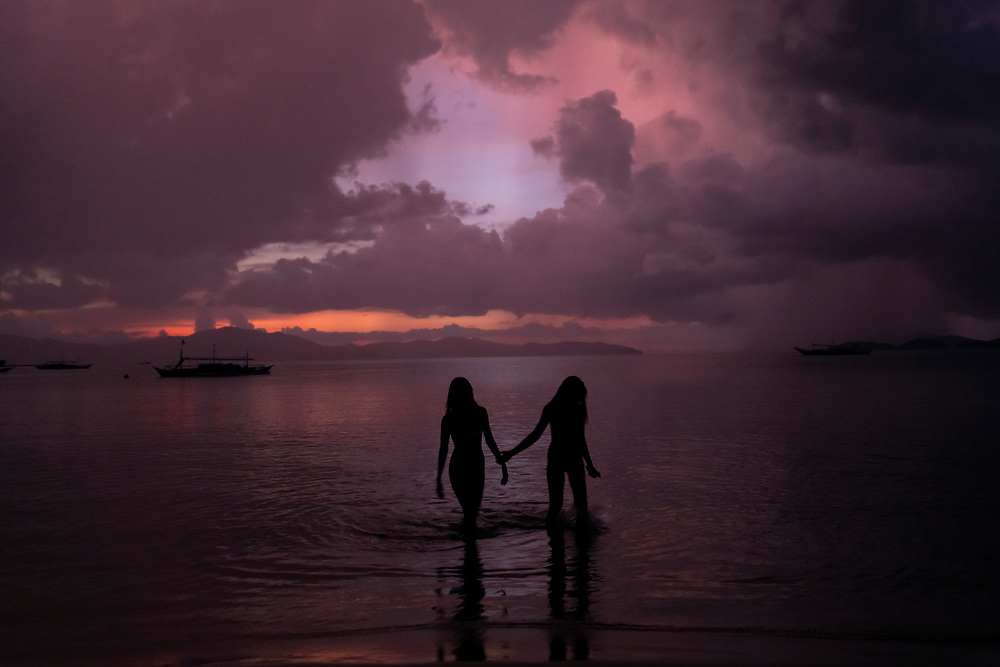 Two friends, both Filipino women, wade in the sea at sunset in Port Barton, Palawan, Philippines. (July 2019)
