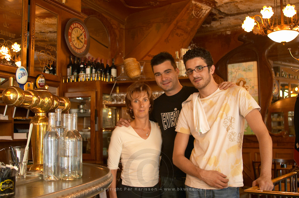 The curved bar zinc brass beer and water taps and water carafes. Bottles and glasses on shelves behind the bar. The bar staff posing for the camera The Bistrot du Peintre is an old fashioned Paris café cafe bar restaurant of art nouveau design with polished brass, mirrors and old signs