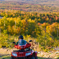 A man rides his ATV on a ridge at Jericho Mountain State Park in Berlin, New Hampshire. White Mountains.