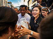 11 NOVEMBER 2016 - BANGKOK, THAILAND: YINGLUCK SHINAWATRA (center right) sells a sack of rice to a man at a rice distribution sale in the Bangkok suburbs. Yingluck Shinawatra, the former Thai Prime Minister deposed in a coup in 2014, has started selling rice directly to Thai consumers. She buys the rice from farmers at market prices and then sells it to urban consumers at the price she paid. She said she's doing it to help out farmers, who are trying to deal with depressed prices. Yingluck is facing prosecution on corruption related charges going back to a rice price support scheme her government used to try to help farmers in 2011 and 2012. Even after the coup, she is still personally popular and hundreds of people showed up to see her at the rice distribution point at a mall in Samut Prakan province, in suburban Bangkok.   PHOTO BY JACK KURTZ