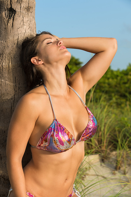 Woman tanning in a beach in swimsuit