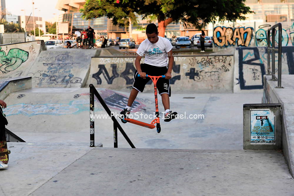 Young teen does stunts with a razor scooter in a skatepark. Photographed at Skaeland, Tel Aviv, Israel