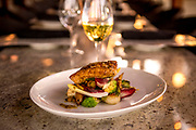 Wild caught Pacific sea bass served with fingerling potatoes, riesling raisins, pistachio, baby endive, cauliflower, capers, and preserved lemon vinaigrette from Olea Restaurant in Newport Beach, CA.
