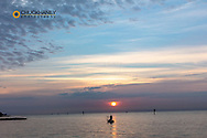 Vivid sunrise clouds over man fishing in the Atlantic Ocean from Higgs Beach in Key West,Florida, USA
