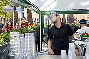 With the Coronavirus pandemic lockdown rules being eased, pubs have now re-opened and staff working under cover outside the riverside Trafalgar Tavern, a pub on the Thames at Greenwich, serve customers wearing required face shields, on 5th July 2020, in London, England.