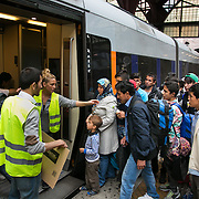 Volunteers at CPH Central station help refugees onboard a train to Sweden and safety.  An unprecedented number of refugees arrived from Germany in early September, most being Syrian war refugees, some from Afghanistan. Most wanted to travel on to Sweden and a number of Danish citizens created a spontanious network to assist the refugees with travel, food, clothes and psycological support.