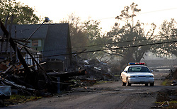 30 Sept, 2005.  New Orleans, Louisiana. Lower 9th ward. Hurricane Katrina aftermath. <br /> The remnants of the lives of ordinary folks, now covered in mud as the flood waters recede. A cops patrol the area as light fades. <br /> Photo; ©Charlie Varley/varleypix.com