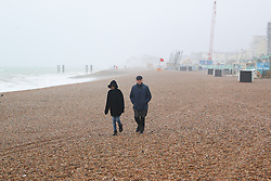 © Licensed to London News Pictures. 31/05/2015. Brighton, UK. A solitary couple takes a walk on the mostly empty beach in Brighton with strong wind and high waves battering the South Coast, today May 31st 2015. Photo credit : Hugo Michiels/LNP