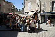 medieval town center with tourist gathering around sales stand