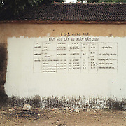 The People's Committee in every village paints instructions for planting and growing rice on a village wall each year, Dong Sai village, Bac Ninh province, Vietnam