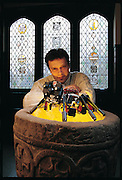 """Photographed at a baptismal font in the chapel of Schloss Burlinghoven, a nineteenth-century castle on the campus of the German National Center for Information Technology, the walking robot Sir Arthur stands with its creator, research scientist Frank Kirchner. Sir Arthur began as a relatively simple robot with sonarlike """"vision"""" that prevented it from trapping itself in corners and snagging itself on obstacles. It was successful enough that Kirchner obtained funding from the U.S. Defense Advanced Research Projects Agency to assemble a team of researchers from diverse disciplines: computer science, math, physics, and electronic and mechanical engineering, to build an enhanced, solar-powered version that can cross rough outdoor terrain. Germany. From the book Robo sapiens: Evolution of a New Species, page 112"""