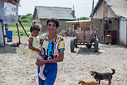 Portrait of mother holding her daughter in the Roma area of Frumusani.