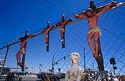 Four crucifixes are hanging on a wire fence a road junction in a Los Angeles suburb. On a bright and clear day, we see the Christian icons against a blue sky, on sale at an outdoor store. The effigies of Jesus are two different sizes, a larger and a smaller and are painted in realistic wood and skin colours with red streaks that symbolise blood emerging from the Holy man's hands, chest, knees and feet where the Roman nails were supposed to have pierced. Other models are seen below the crosses - models of animal garden ornaments and mantelpiece furniture.