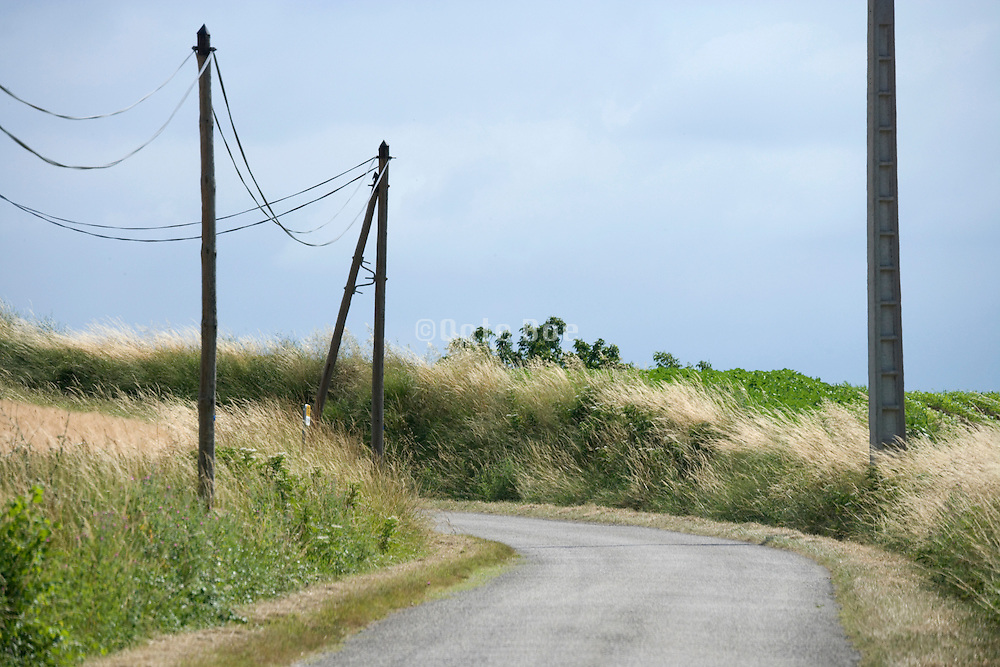 small rural French countryside road with telephone wires