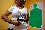"""Javondlynn Dunagan of JMD Defense and Investigations holds her Smith and Wesson M&P Shield 9mm gun in her training classroom in Chicago, Illinois. Dunagan hosts a """"Ladies of Steel Gun Club"""" and teaches concealed-carry classes to women. AFP Photo/Jim Young"""