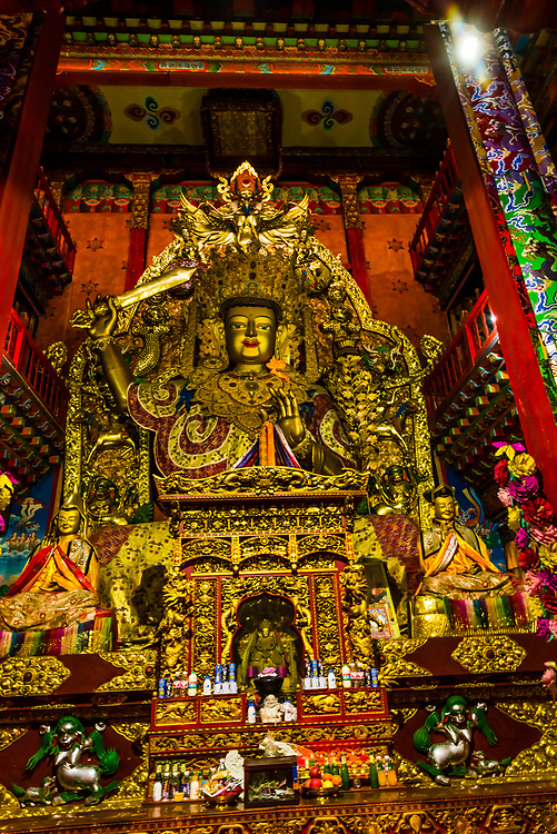 Buddha statue in prayer hall, Songzanlin (Ganden Sumtsenling) Monastery, Shangri La, Yunnan Province, China. It is the largest Tibetan Buddhist monastery in Yunnan Province.
