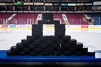 KELOWNA, CANADA - JANUARY 9: Hockey pucks stand on the boards on January 9, 2019 at Prospera Place in Kelowna, British Columbia, Canada.  (Photo by Marissa Baecker/Shoot the Breeze)