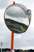 farm and rice paddies reflecting in road safety round mirror Japan