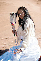 """Modern American Indian Woman holding her hand in the yoga mudra.<br /> :::<br /> """"The man who sat on the ground in his tipi meditating on life and its meaning, accepting the kinship of all creatures and acknowledging unity with the universe of things, was infusing into his being the true essence of civilization.""""<br />  -Luther Standing Bear Native American Navajo Woman Yogini. Diné woman practicing yoga in her indigenous red earth environment."""