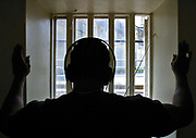 A prisoner in his cell listens  to Radio Wanno, the prisons community radio station through headphones. HMP Wandsworth, London, United Kingdom.
