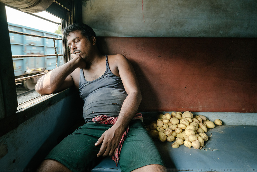 """One of the cooks takes a break next to a pile of peeled potatoes in the kitchen's """"pantry"""" compartment.<br /> Inside the Dibrugarh-Kanyakumari Vivek Express, the longest train route in the Indian Subcontinent. It joins Kanyakumari, Tamil Nadu, which is the southernmost tip of mainland India to Dibrugarh in Assam province, near the border with Burma."""