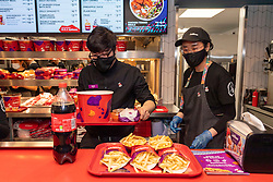© Licensed to London News Pictures. 20/05/2021. London, UK. Staff members with food orders at the new Jollibee fried chicken flagship restaurant in Leicester Square, West End. Established in 1978, the Filipino fast food company has over 1300 restaurants worldwide. Photo credit: Ray Tang/LNP