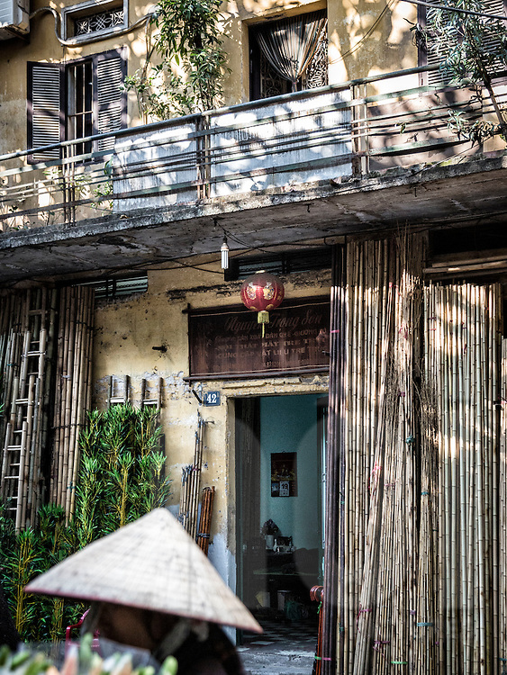 Bamboo poles stand against the facade of a shop along Hang Vai street known for bamboo products in Hanoi's Old Quarter, Vietnam, Southeast Asia