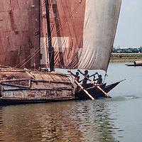 A sailboat carries cargo up a river near Dhaka, Bangladesh.