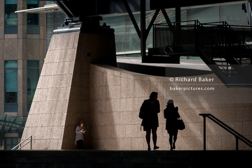 Silhouettes of two women walking through the Broadgate corporate offices development in the City of London. Another female uses a personal mobile device in a quiet corner as the two ladies walk together, going under the tall steel architecture with the backdrop of the Broadgate development within the ancient boundary of the capital's Square Mile, it's financial district founded by the Romans in AD43.