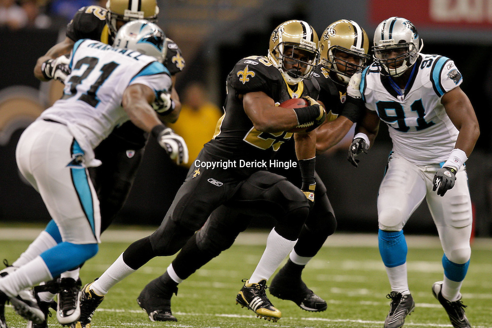 Nov 08, 2009; New Orleans, LA, USA;  New Orleans Saints running back Reggie Bush (25) runs between Carolina Panthers defenders defensive end Everette Brown (91) and cornerback Richard Marshall (31) during second half at the Louisiana Superdome. The Saints defeated the Panthers 30-20. Mandatory Credit: Derick E. Hingle