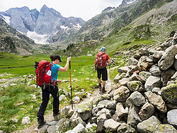Man and woman hiking in the High Pyrenees in front of mount Vignemale, Cauterets, France