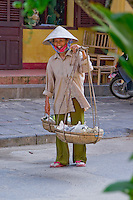 A female street vendor wearing a conical hat selling fruit in the streets of Hoi An's old town.