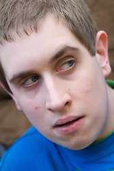 Portrait of teenage boy with Autism; looking thoughtful,