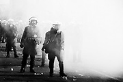 """Athens, greece - Riot police standing amid tear gas near the Parliament. Greek economical crisis started in 2008. The so-called Austerity measures imposed to the country by the """"Troika"""" (European Union, European Central Bank, and International Monetary Fund) to reduce its debt, were followed by a deep recession and the worsening of life conditions for millions of people. Unemployment rate grew from 8.5% in 2008 to 25% in 2012 (source: Hellenic Statistical Authority). <br /> Bruno Simões Castanheira"""