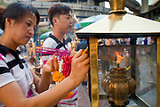 25 MARCH 2010 - BANGKOK, THAILAND: People light candles before praying at the Erawan Shrine in Bangkok. The Erawan Shrine (Thai: San Phra Phrom) is a Hindu shrine in Bangkok, Thailand that houses a statue of Phra Phrom, the Thai representation of the Hindu creation god Brahma. The Erawan Shrine was built in 1956 as part of the government-owned Erawan Hotel to eliminate the bad karma believed caused by laying the foundations on the wrong date..The hotel's construction was delayed by a series of mishaps, including cost overruns, injuries to laborers, and the loss of a shipload of Italian marble intended for the building. Furthermore, the Ratchaprasong Intersection had once been used to put criminals on public display. An astrologer advised building the shrine to counter the negative influences. The Brahma statue was designed and built by the Department of Fine Arts and enshrined on 9 November 1956. The hotel's construction thereafter proceeded without further incident.      PHOTO BY JACK KURTZ