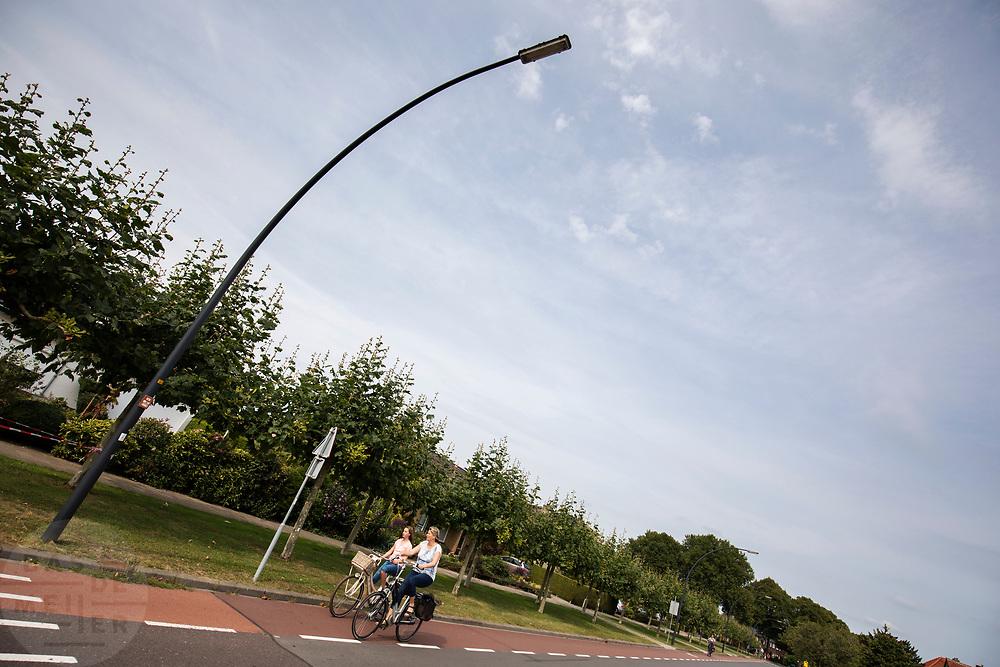 In Zevenaar rijden fietsers door de Molenstraat.<br /> <br /> Cyclists in Zevenaar, a suburban in the eastern part of The Netherlands.