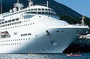 Alaska. Southeast, Ketchikan. Port of Call, Sea kayaking beneath Princess Regal cruise ship.