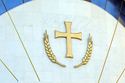 Cross and ears of wheat symbolising the body of Christ and the bread taken during the service of Holy Communion above the main door  of the Resurrection of Christ Orthodox Cathedral of Tirana. Triana, Albania. 02Sep15